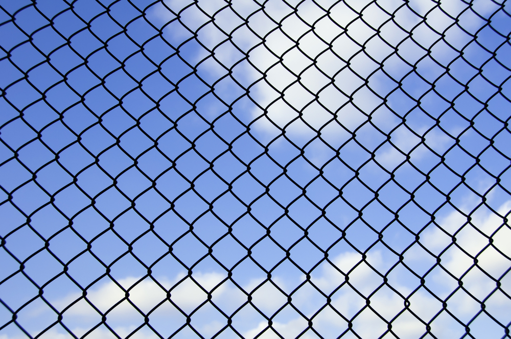 Barrier to dreams Mesh fence with partly cloudy sky beyond