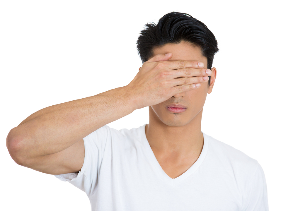 Closeup portrait of young man, closing, covering blind eyes with hands cant see, hiding, avoiding situation, isolated on white background. See no evil concept. Human emotions, facial expressions