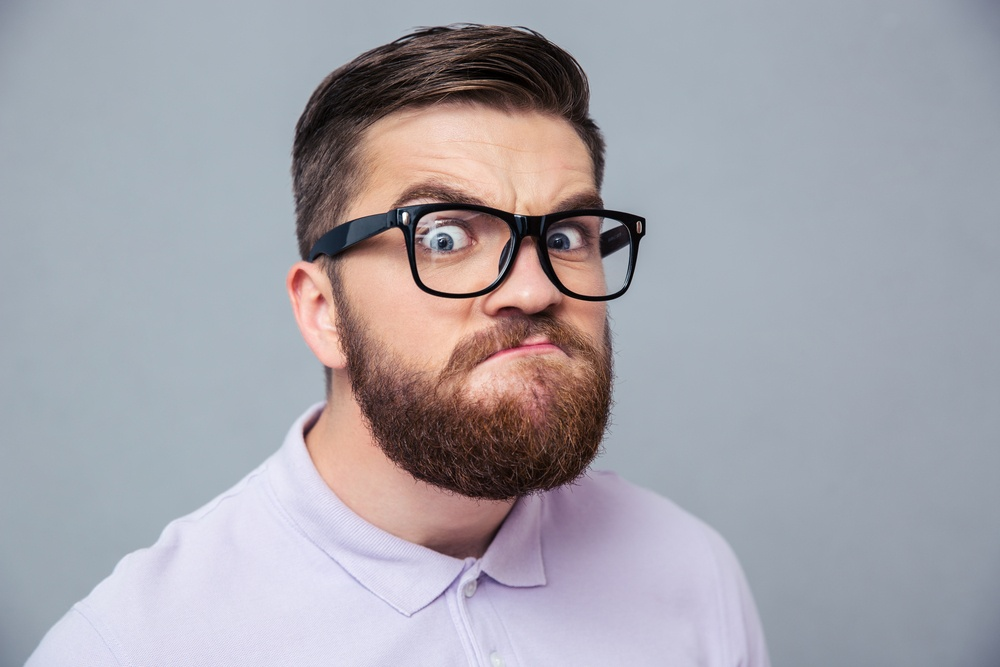 Portrait of a funny hipster man looking at camera over gray background
