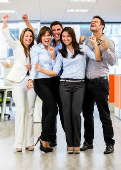 Successful business team at the office with arms up