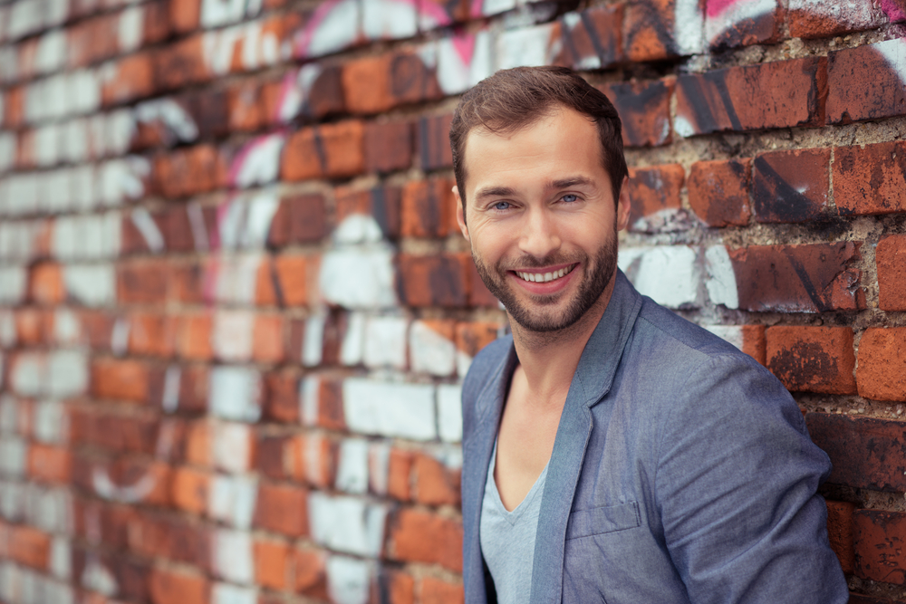 Close up Happy Handsome Man in Trendy Fashion Leaning on Old Brick Wall While Looking at the Camera.